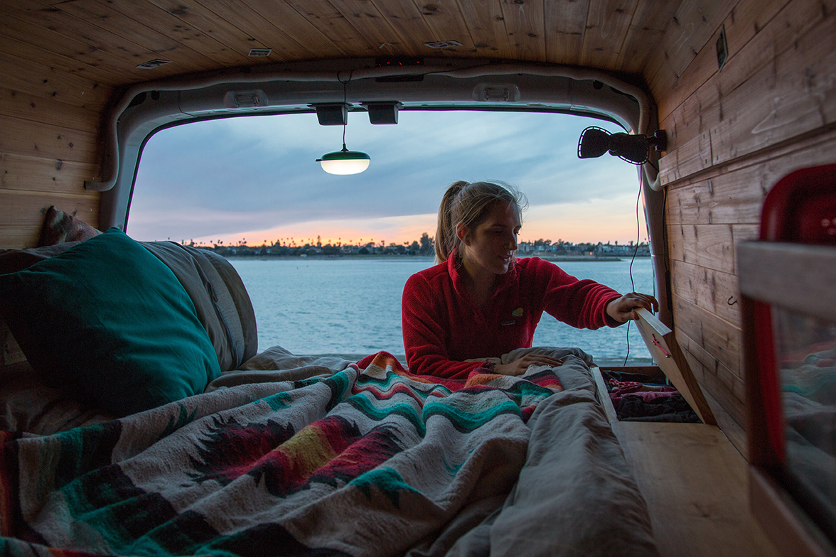 A woman inspects a storage compartment in in the back of her camper van with water in the background.