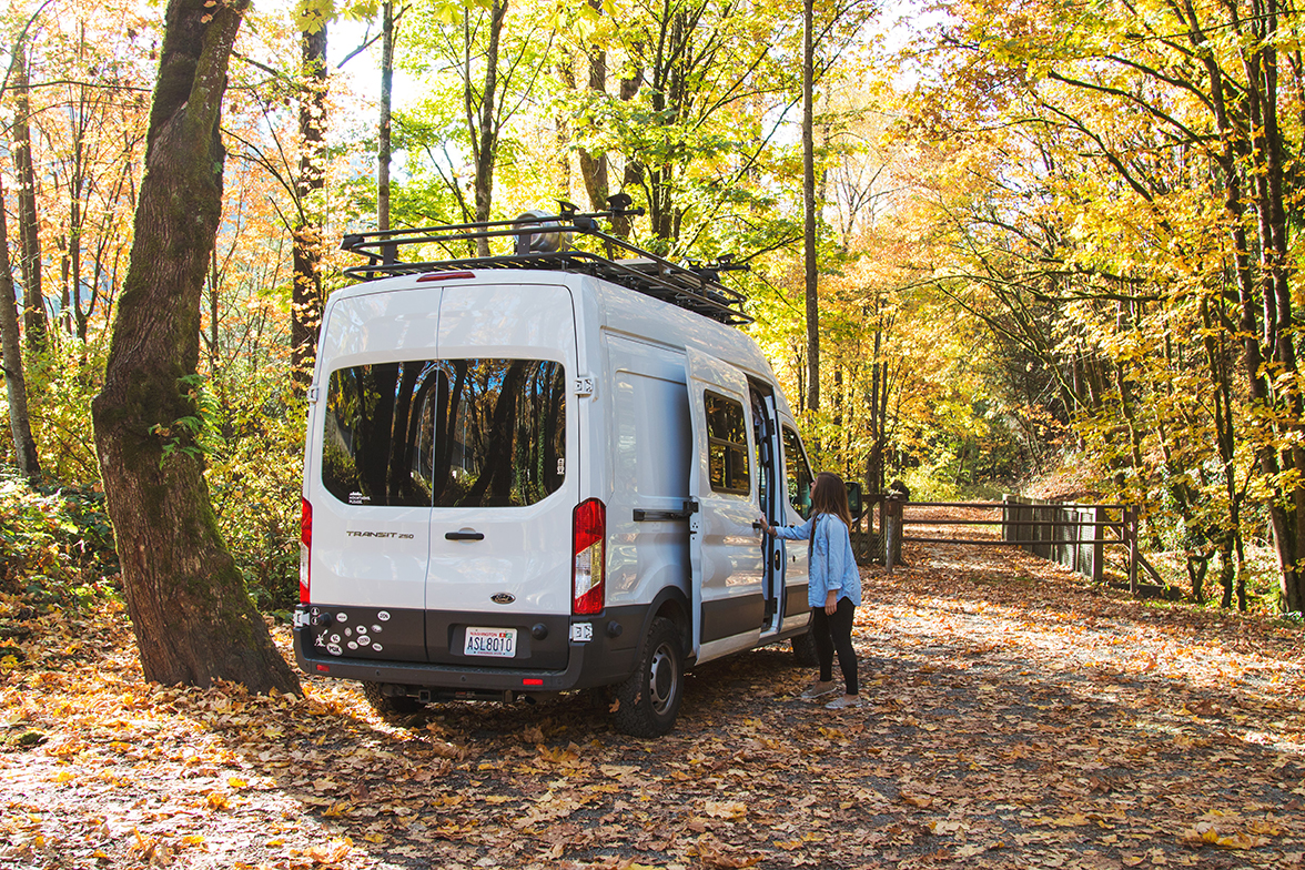 A woman opens the sliding door of her white camper van parked on leaf-covered asphalt as fall leaves adorn the trees.