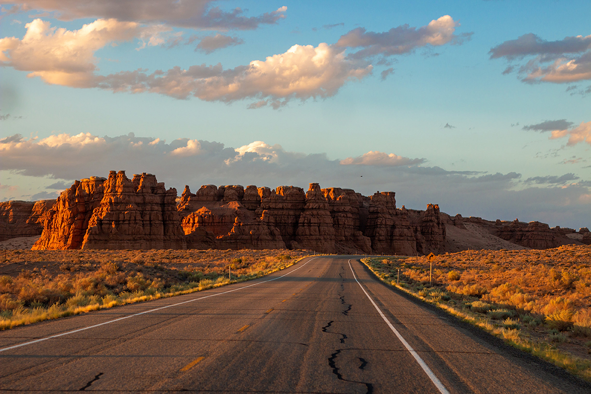 A desert highway veers right to skirt the rugged rock faces of a bluff on the horizon.