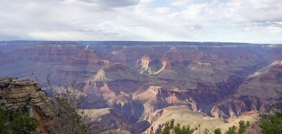 A view of the vast Grand Canyon from a rim, with late-day shadows blanketing the buttes, ravines and rock faces of the mile-deep geological marvel.