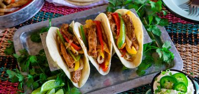 Pressure cook flavorful fajitas — A row of three fajitas filled with meat and cooked peppers.
