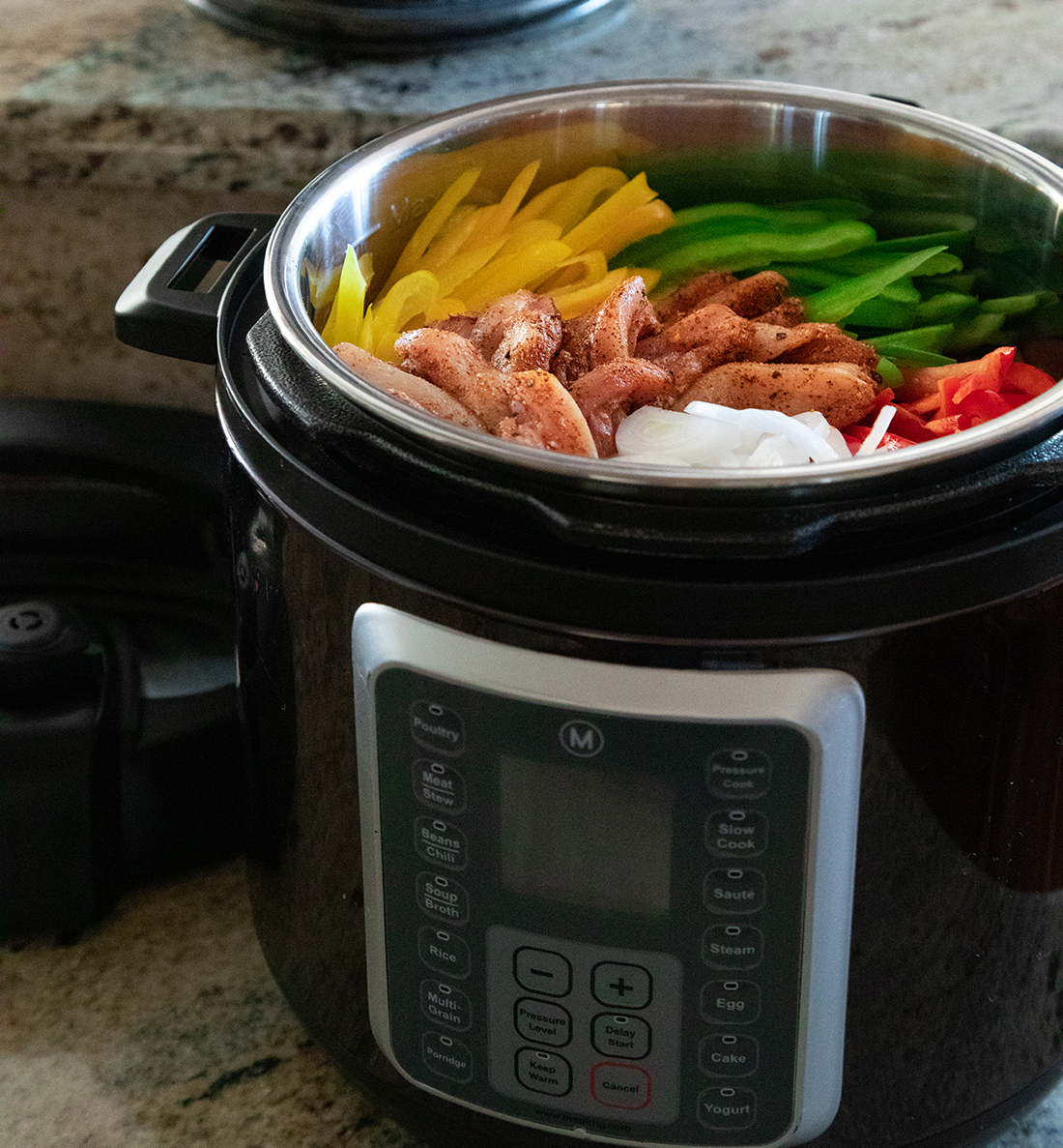A pressure cooker filled with onions, chicken and red, green and yellow peppers.
