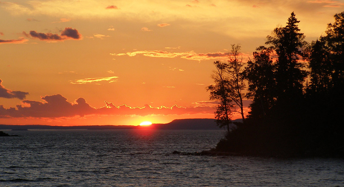 The sun descends behind the horizon of a great lake. Foreground: trees grow in a rugged shoreline.