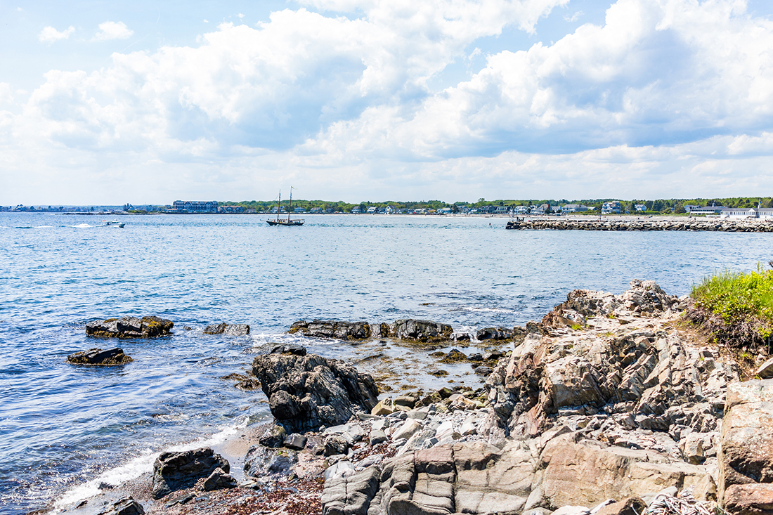 A ship floats in the distance off a rugged coastline in Maine.