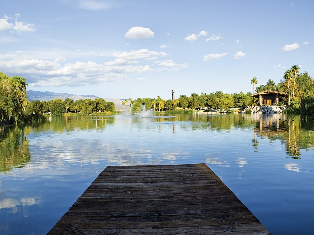 A wooden dock juts into a lake that reflects clear blue skies along with the palm trees that grow on the bank.