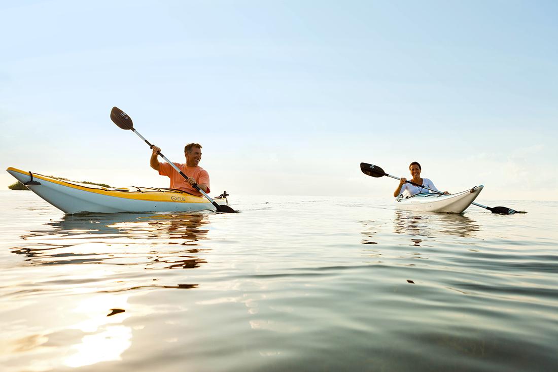 kayaking florida lower keysA couple smile at eachother as they kayak across placid water.