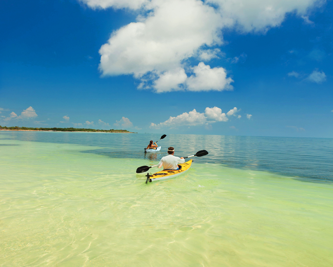kayaking florida's lower keys A couple paddle in individual kayaks across clear shallow ocean water.