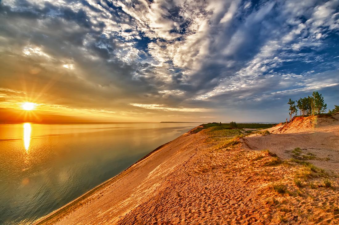 Sloping sandy beach leads to a vast lake below.