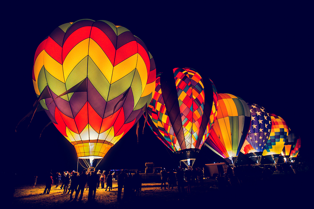 A row of balloons glowing from within in the night.