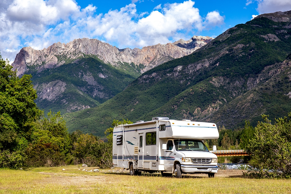 A Class C motorhome parked in an empty field with mountains rising sharply in the background.