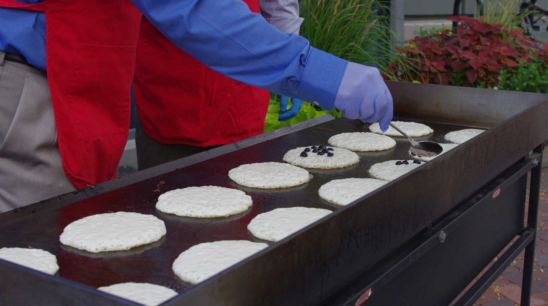 A person lays down pancakes on a griddle