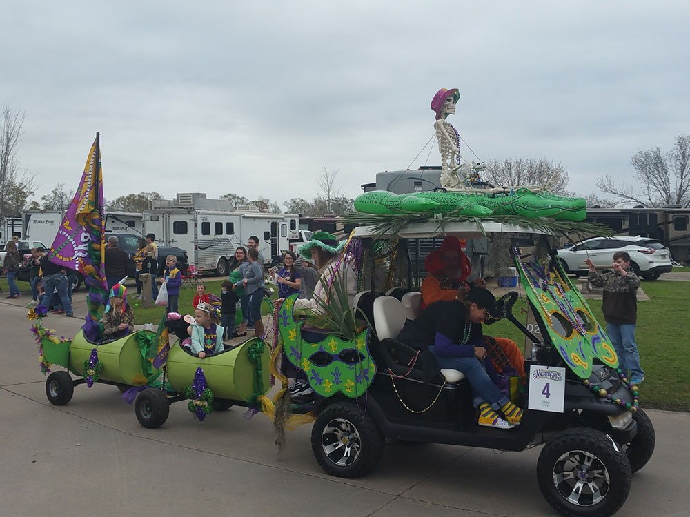 An ATV pulls two cars as part of a kid-friendly Mardi Gras parade.
