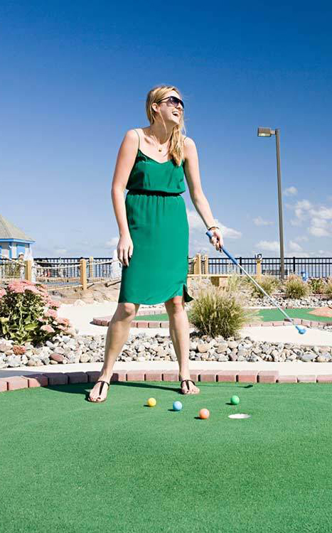 A woman in a green dress plays miniature golf with multi-colored balls.
