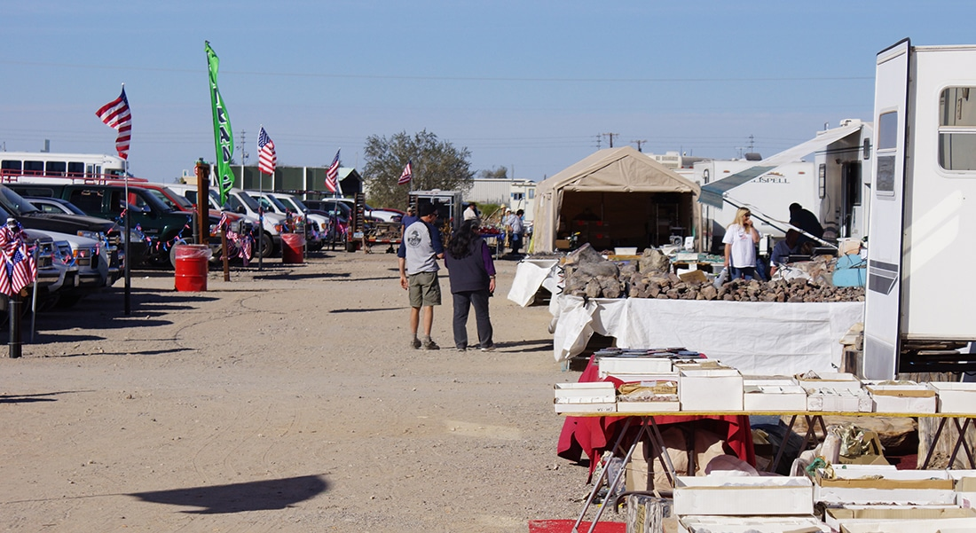 A couple strolls past rocks and books sold on tables set up outside of RVs.