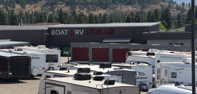 Trailers and motorhomes in an RV & Boat Storage yard.