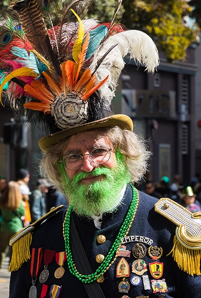 A dude with a green beard and feathered hat marches in an Irish parade.