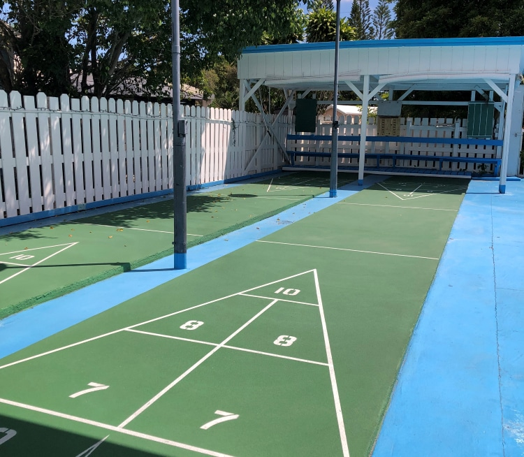 Two shuffleboard courts running parallel to a wooden picket fence.