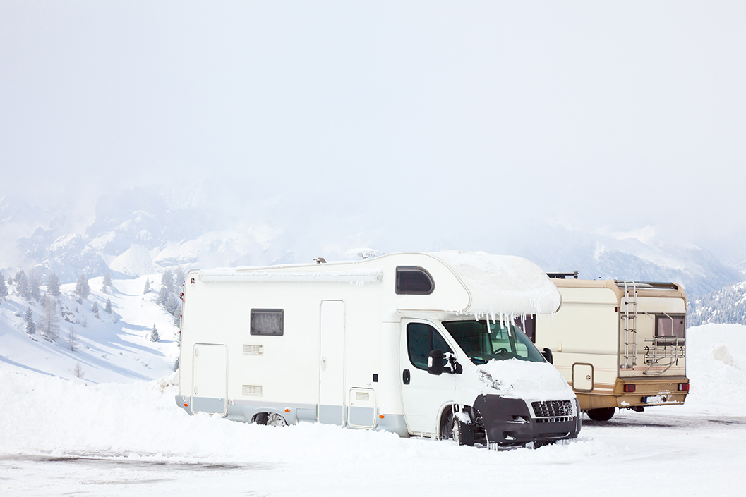 An RV covered with snow with icicles.