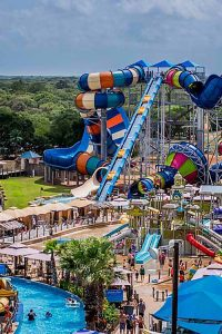 A colorful complex of water slides and pools with bathers cavorting in all the fun.