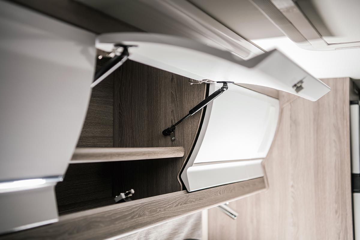 The open door of an overhead cabinet in an RV interior.
