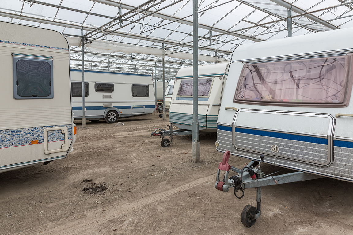 RVs in storage under a roof.