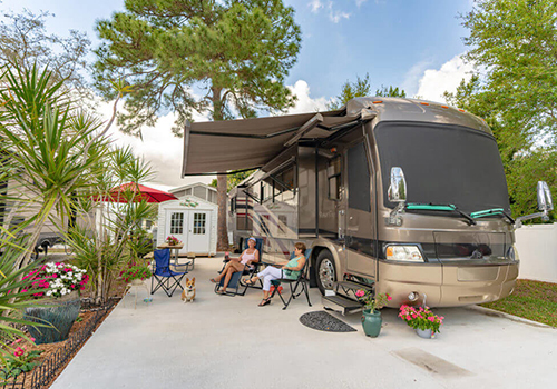 Three women lounge under the extended awning of a large, tan motorhome on a concrete slab.