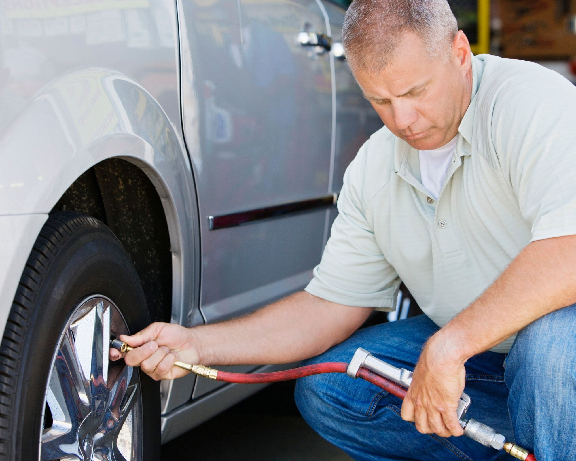 A squatting man pumps up the tire to a silver vehicle.