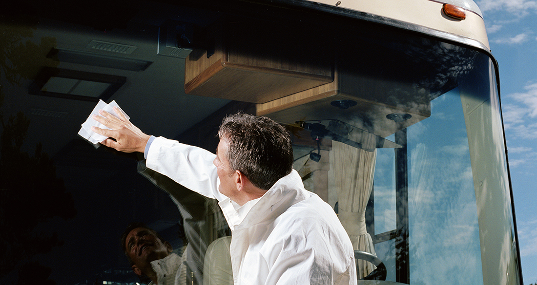 winter rv storage steps — Man cleaning coach bus windshield, side view, under blue sky