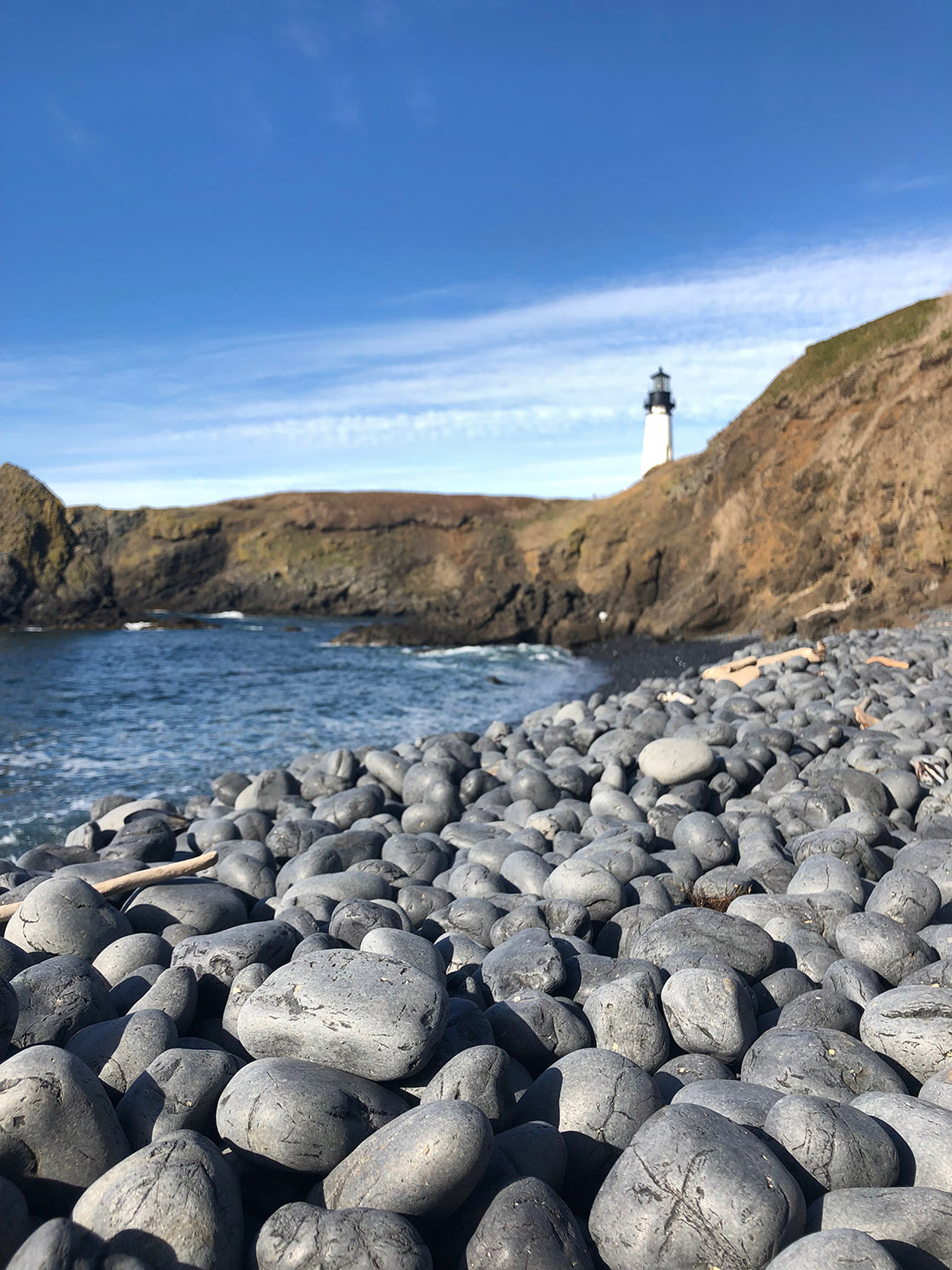 A rocky beach stretches into the background toward some cliffs, upon which a lighthouse is perched.