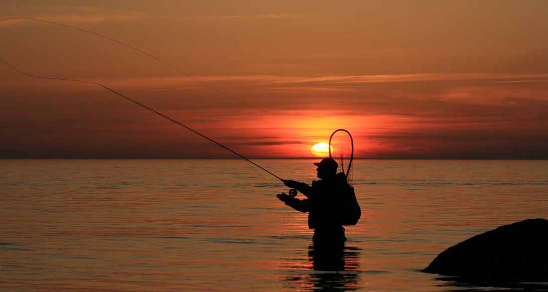 An angler in hip deep water casts a line as the sun sets behind him.