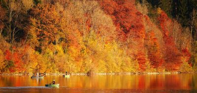 Anglers with lines in the water float in small fishing boats with the background golden fall foliage reflected on the lake.