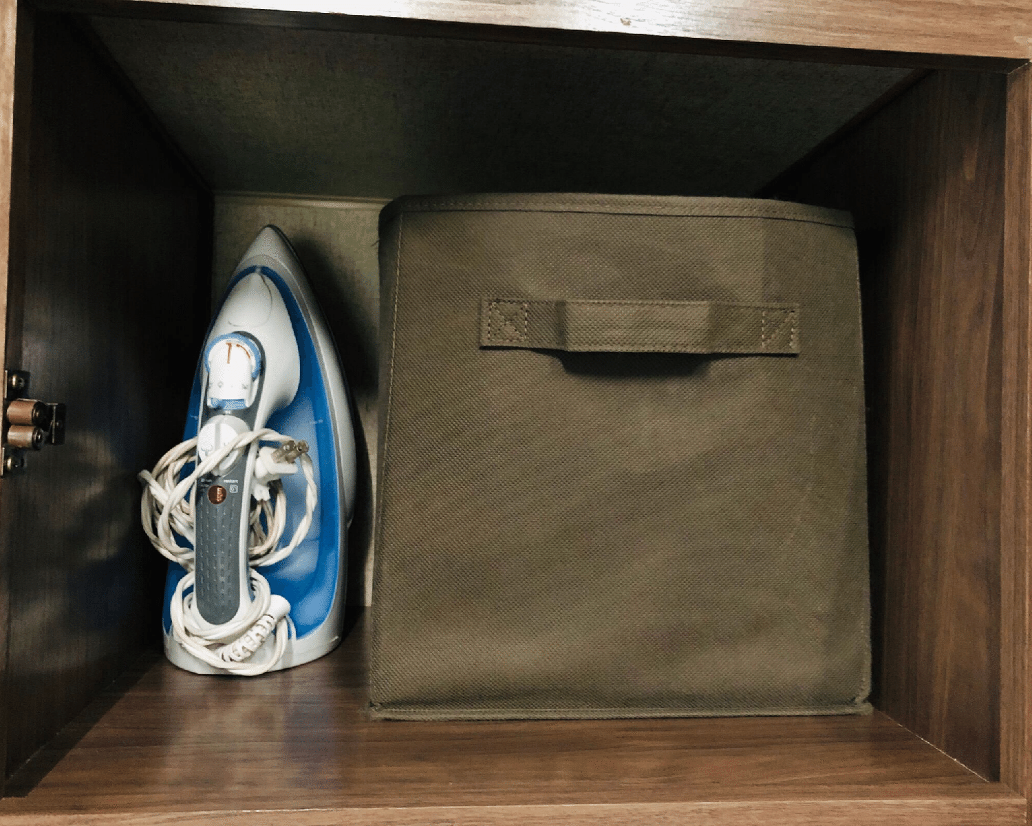 An iron and fabric bin stowed in a storage compartment.