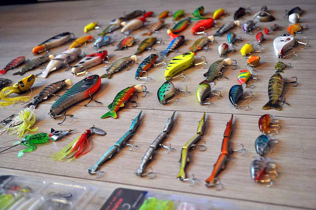 An array of about 50 colorful fishing lures on a wooden table.