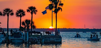 New Good Sam Parks September — Sunset over boats with silhouetts of palm trees.