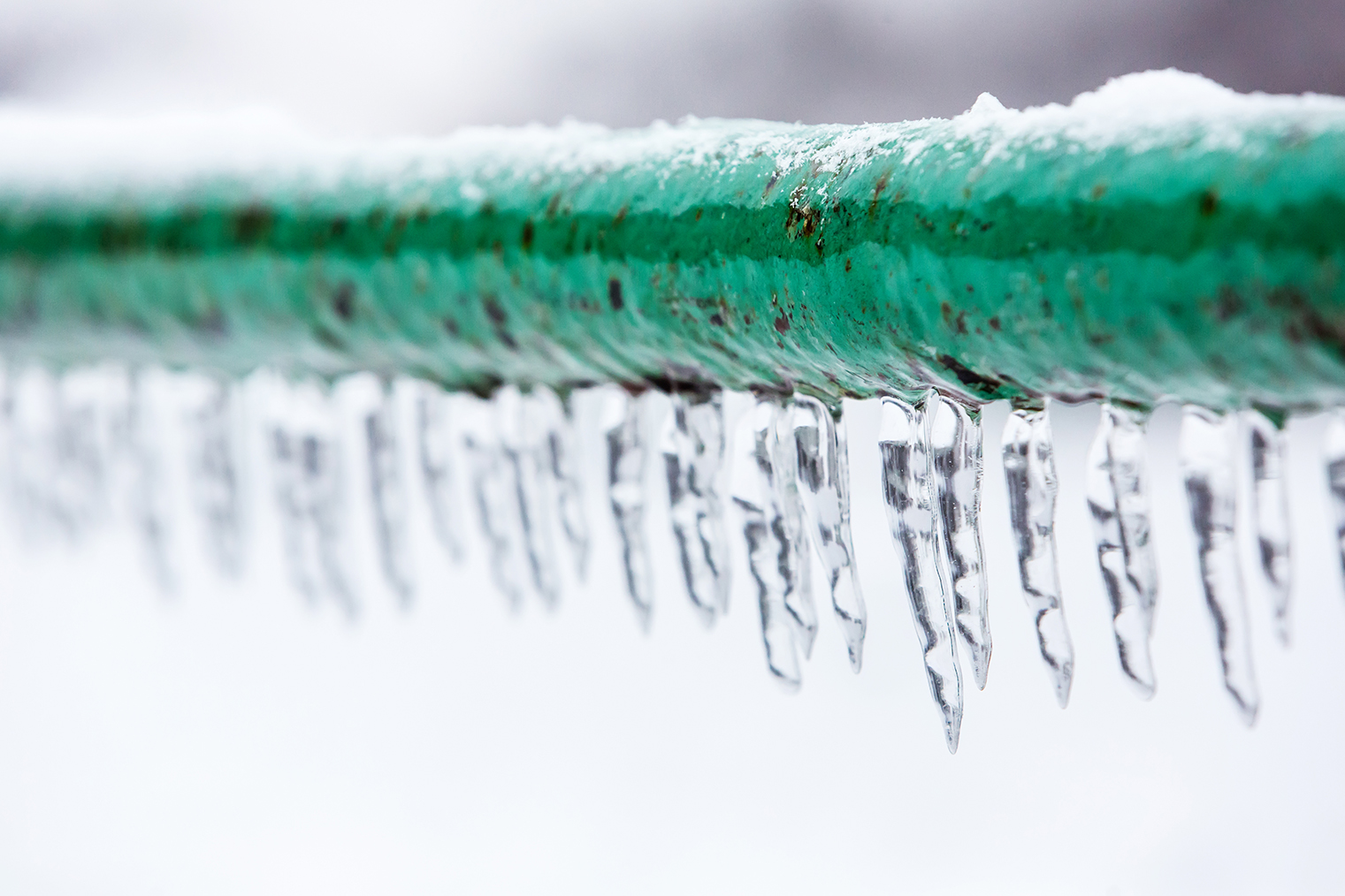 A frozen green hose with icicles hanging from it.