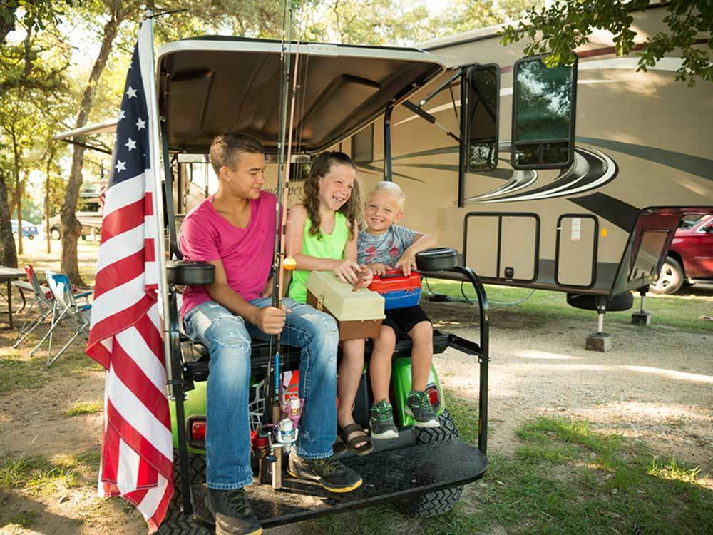 Three kids holding fishing poles sits in the back of an ATV with fifth-wheel in the background and American flag in the foreground.