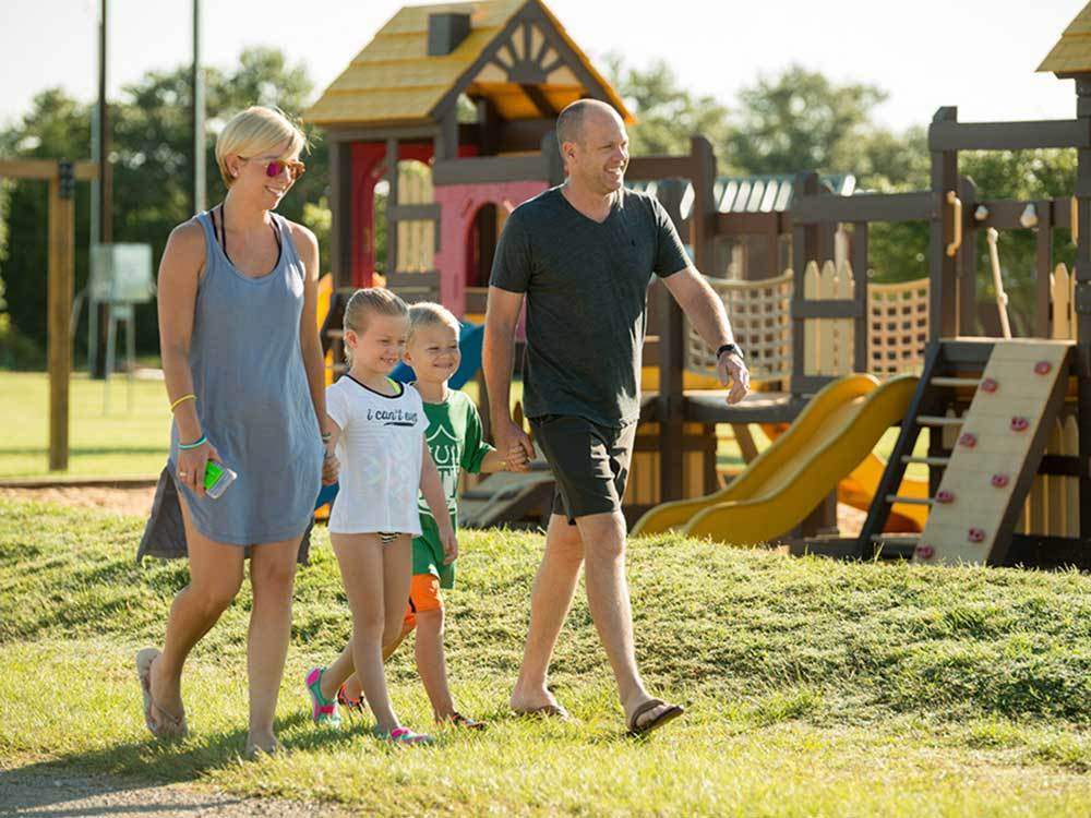 Two kids flanked by their parents walk hand-hand-in-hand past some play structures.