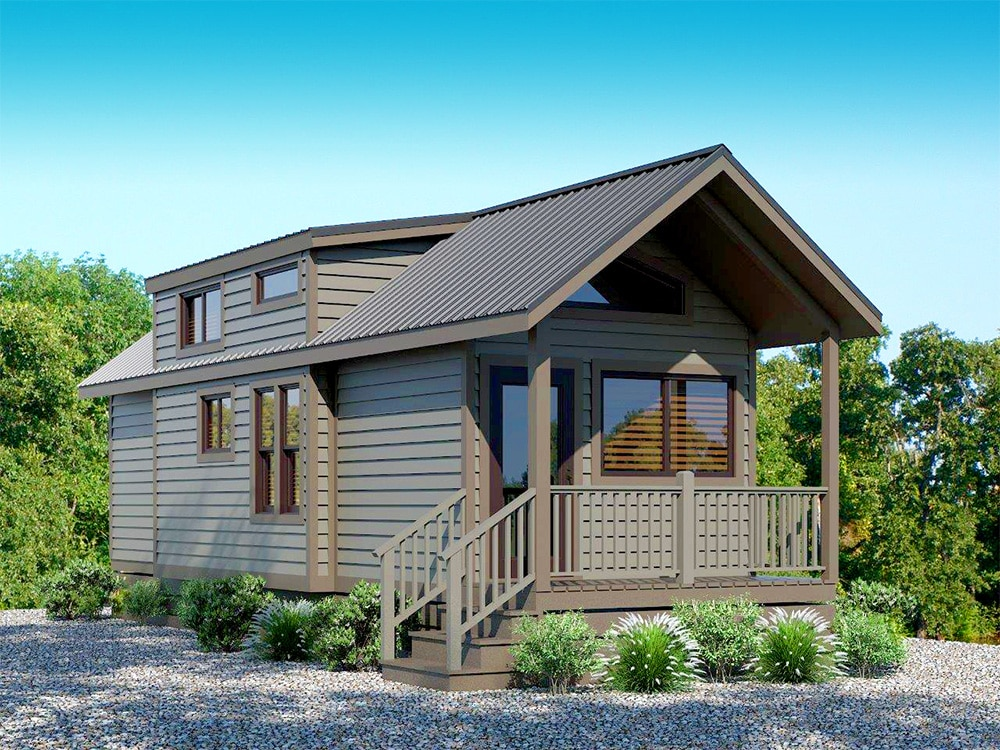 A brown camping cottage with a front porch accessible by stairs and surrounded by tasteful landscaping.