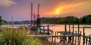 The sun sets over a wooden dock in a river or channel with a lone fishing vessel moored on serene water.