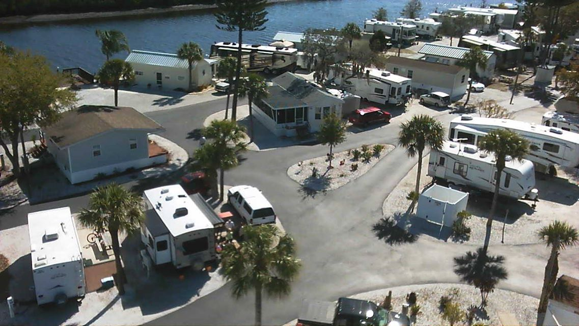 Aerial view of an RV park with park models, motorhomes and trailers. Palm trees grow in the park.