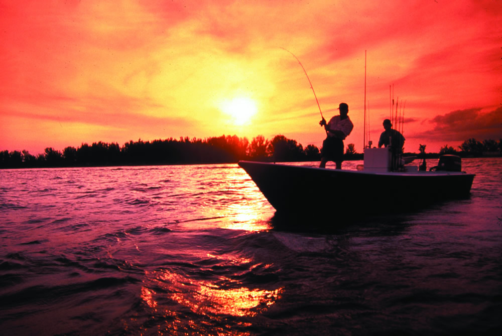 An angler stands in a boat as he pulls on a fish, his rod bent by the strain.