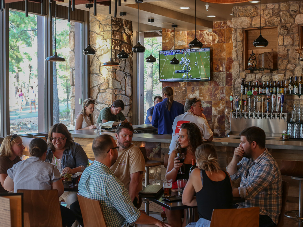 Patrons of a restaurant chat around a pair of tables with a bar in the background as a TV mounted on the wall shows football.