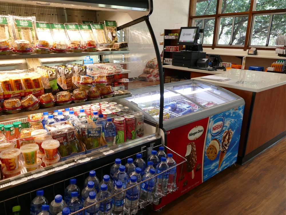 Food displayed in an open convenience-store fridge next to a Hagen Daz and Nestle freezer unit.