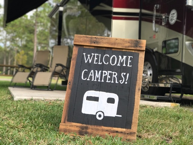 "A ""welcome campers"" sign -- white letters against black background -- propped up with motorhome in background."