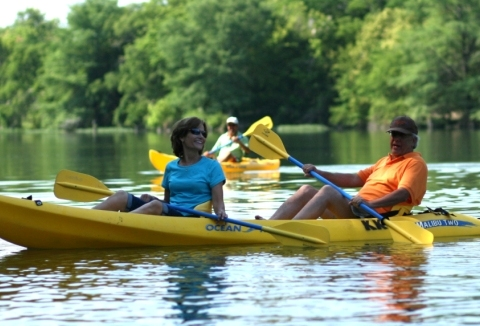 A middle-aged man and woman laugh as they paddle a yellow double kayak.