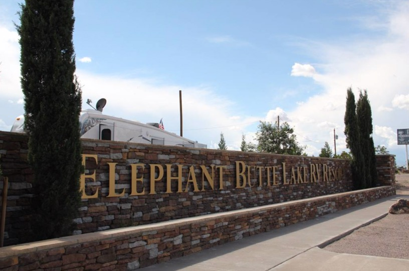 Elephant Butte sign made of metal letters on brick with Italian cypress rising on each side.