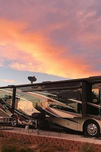 A motorhome with brown and tan graphics against a sunset sky with light burning red on low hanging clouds.