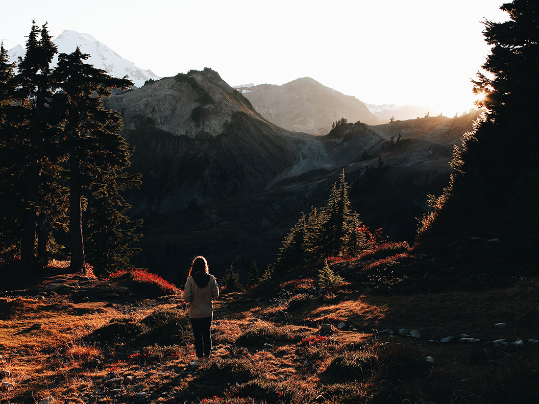 A lone hiker gazes at a setting sun that casts its last rays over a horizon of rugged mountains and upon an autumn-speckled landscape.