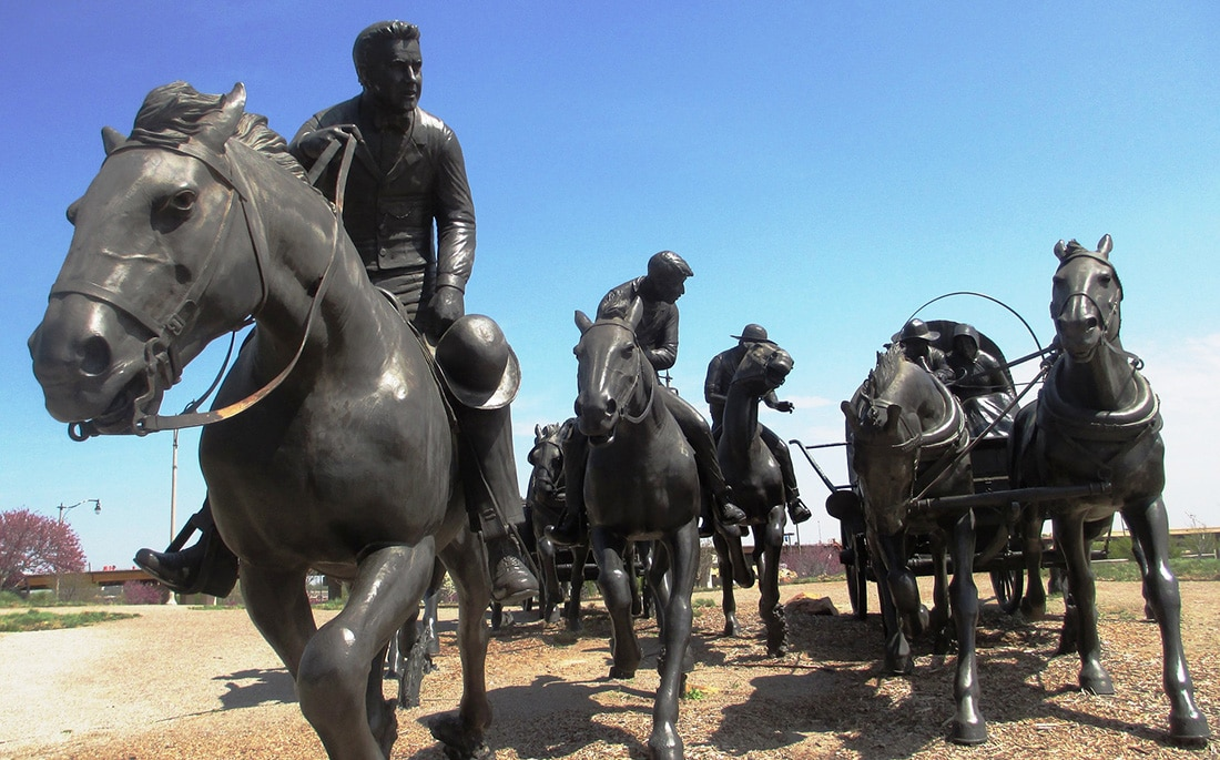 A statue depicting horse riders and covered wagons in a rush for land.