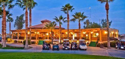 An Arizona resort under tall palms turns on its light as dusk descends.